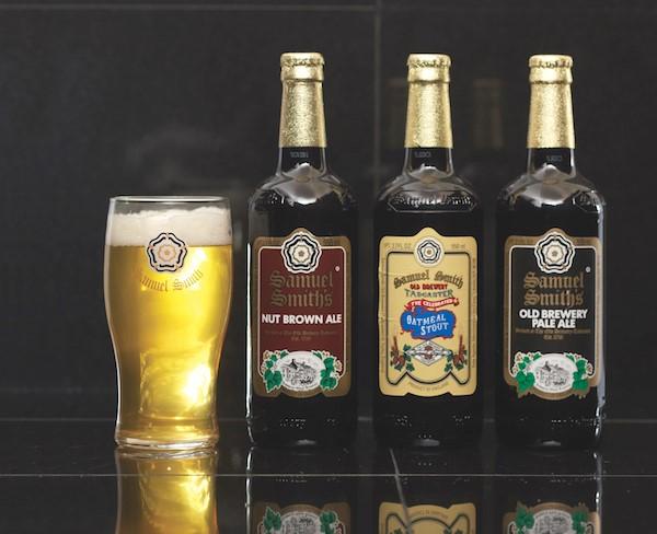 Three craft beer bottles next to beer in pilsner glass