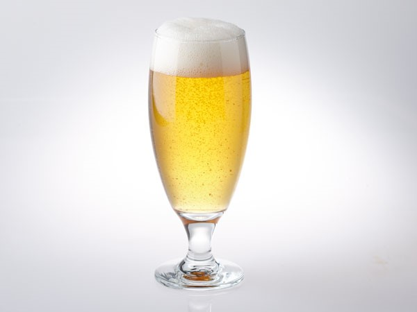 American wheat light beer in glass with foam