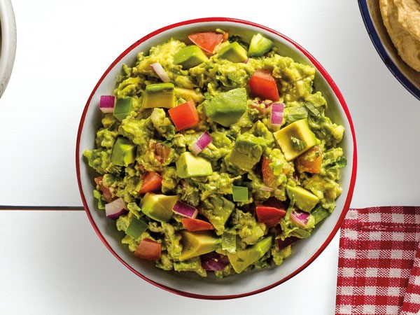 Red-rimmed bowl of guacamole with avocado chunks, red onion and tomato