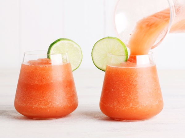 Two glasses of strawberry frozen slushy, garnished with lime slices
