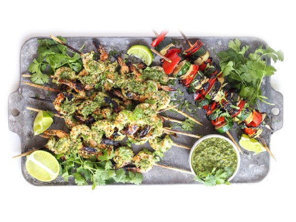 Platter of grilled shrimp covered in chimichurri sauce on skewers next to skewered vegetables