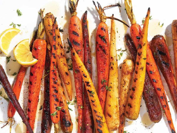 Grilled carrots covered in honey-lemon sauce and garnished with thyme and lemon wedges