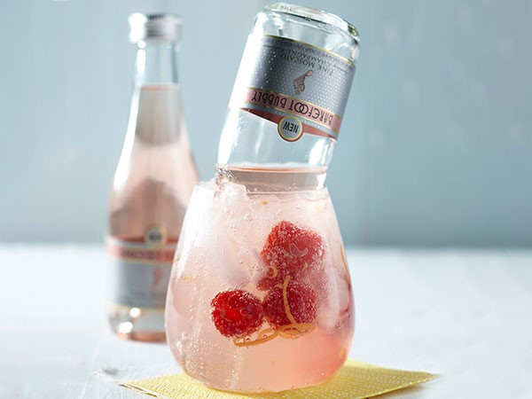 Glass filled with cherry-berry sangria, raspberries and orange zest with a Barefoot Bubbly floater