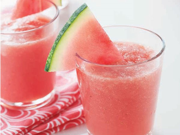 Glass of pink slushie, garnished with a watermelon wedge