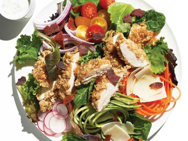 Plate of salad topped with crispy chicken, radishes, red onion, carrots, cherry tomatoes and bacon bits, served with a side of dressing