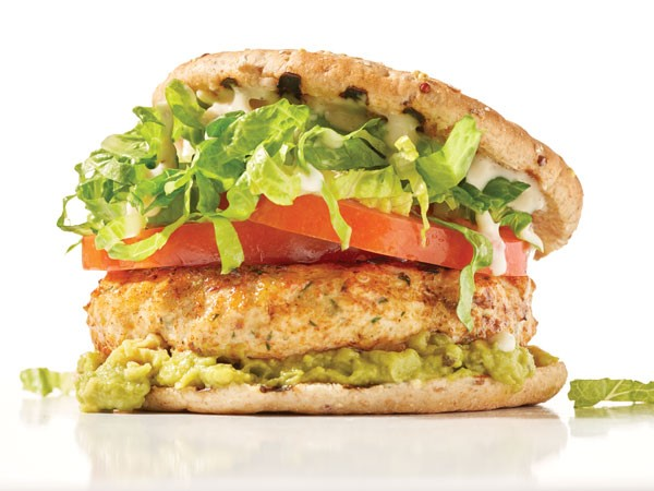 Chicken breast with lettuce, tomato, onion, guacamole and yogurt dressing sandwiched between a split sandwich thin