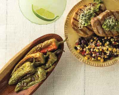 Grilled whole hatch chile peppers next to a plate of pork chops and bean salsa