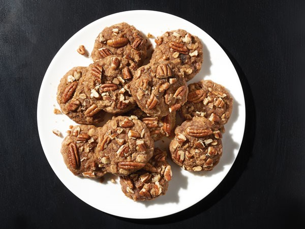 Platter of chocolate banana oatmeal cookies topped with pecans