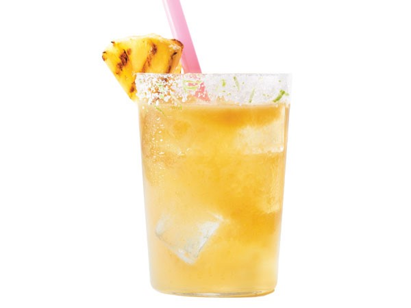 Sugar-rimmed glass of pineapple margarita, garnished with a pink straw and grilled pineapple wedge