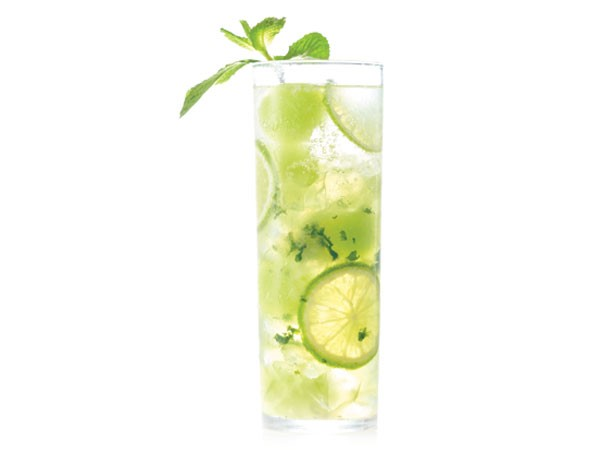 Tall glass filled with honeydew mojito, ice, chunks of honeydew, lime and fresh mint