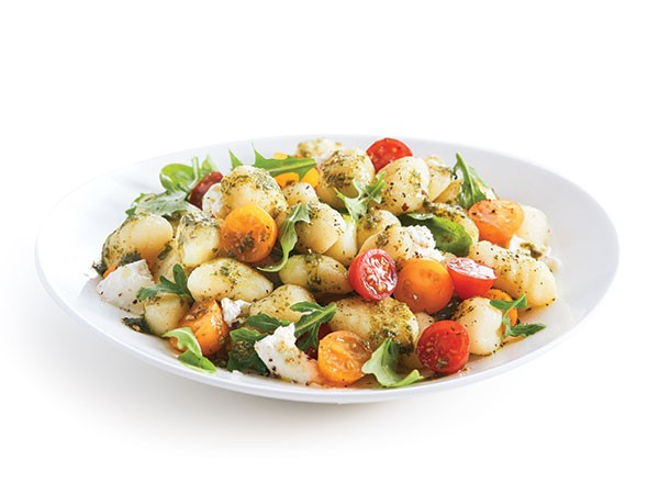 Bowl of salad mixed with gnocchi and grape tomatoes