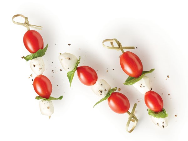 Cherry tomatoes, basil leaves and mozzarella balls on a wooden skewer and covered in freshly ground black pepper