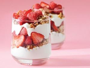 Glasses layered with yogurt, granola and strawberries and raspberries