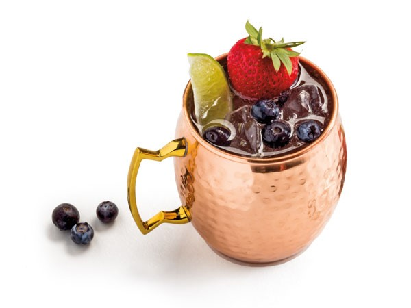 Copper cup filled with berry-flavored moscow mule, garnished with fresh blueberries, strawberries and lime