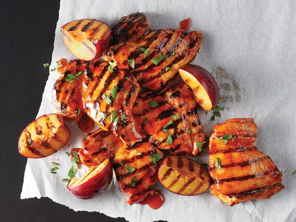 Honey-sriracha grilled chicken thighs served with grilled peaches on parchment paper