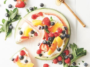 Round watermelon slice topped with yogurt and fresh berries.
