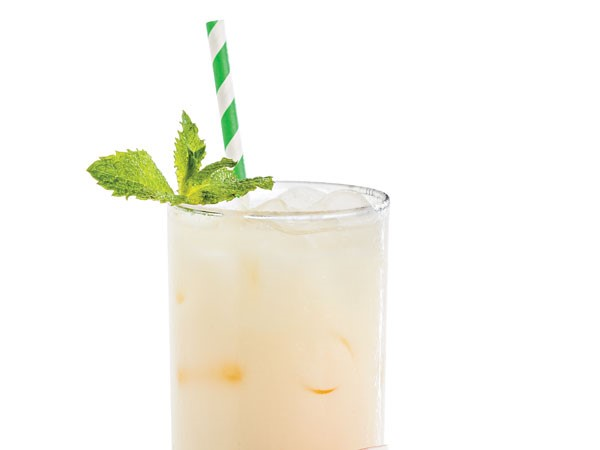 Glass filled with bourbon colada with a green-and-white striped straw