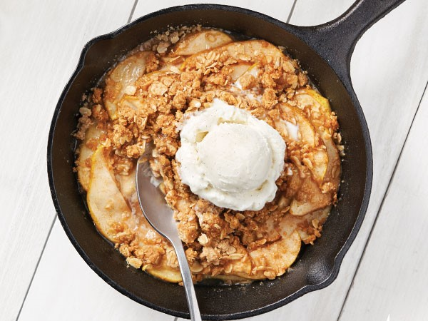 Cinnamon spiced pear crisp served in a cast-iron skillet topped with a scoop of vanilla bean ice cream