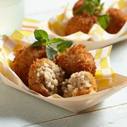 Paper basket filled with baked mushroom arancini balls