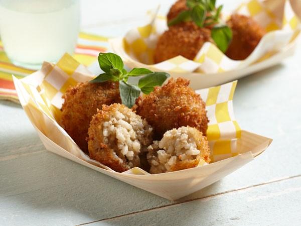 Paper basket filled with baked mushroom arancini balls