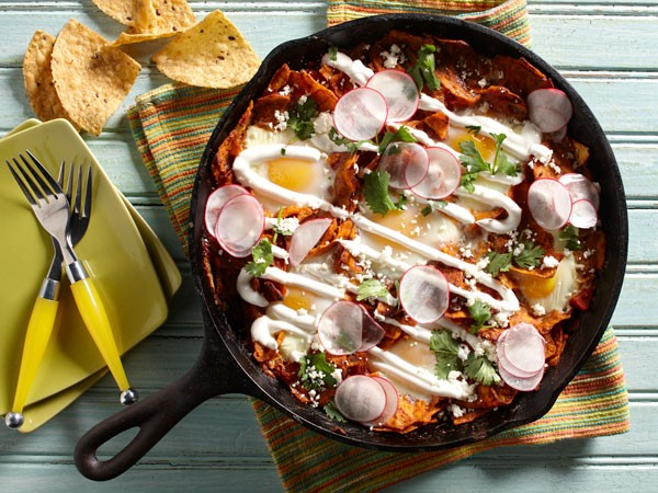 Harissa chilaquiles skillet topped with sour cream, cotija cheese and thinly sliced radishes