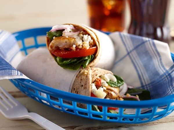Two chicken gyro wraps in a blue basket with a blue-and-white napkin