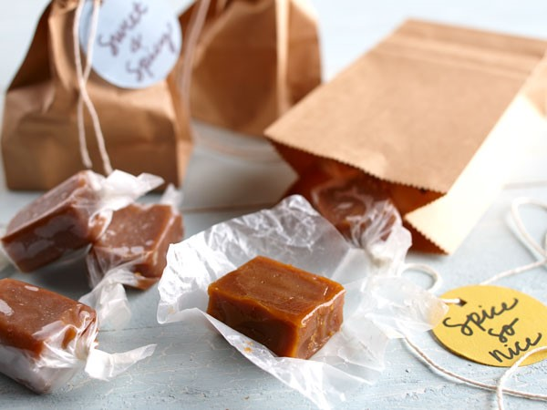 Wax-paper wrapped caramel squares and decorated brown paper bags