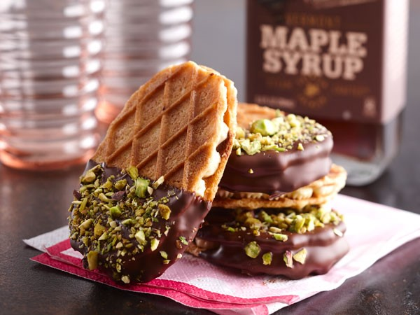 Salted caramel buttercream sandwiched between two waffle crisp cookies and partially dipped in dark chocolate and covered in chopped pistachios