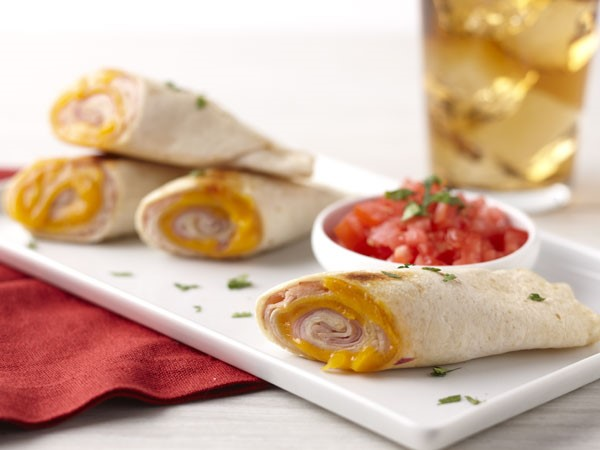 Flour tortillas filled with cheddar cheese, turkey slices and honey ham slices, served on a white board with a side of salsa
