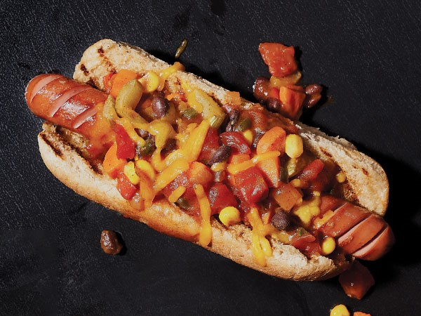 Chili dog topped with mustard, tomatoes, onion and cheese
