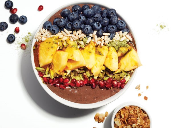 Smoothie bowl topped with pomegranate seeds, nuts, pineapple and blueberries