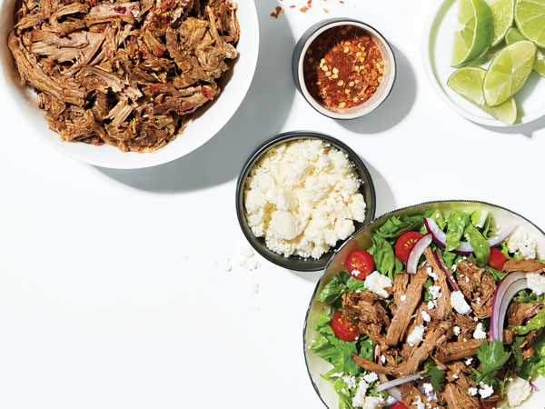 Bowl of beef barbacoa mixed with greens near smaller bowls of cheese, red pepper flakes, lime and beef