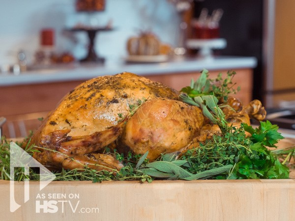 Whole roasted turkey on a bed of herbs