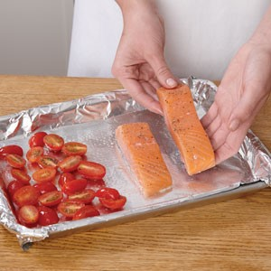 place tomatoes and salmon on sheetpan
