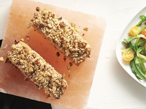 Walnut crusted salmon on a square block next to a plate of veggies on a white background.