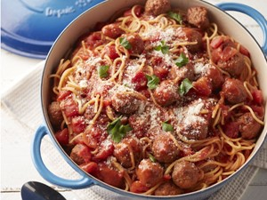 Spaghetti and meatballs in Dutch oven topped with cheese and fresh parsley