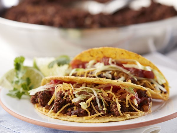 Crunchy shell beef tacos on a plate topped with cheese