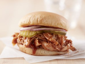 Barbecue chicken on sandwich topped with pickles and red onions