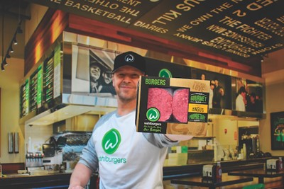 Donnie Wahlberg holding up a package of Wahlburgers at Home Angus beef patties.