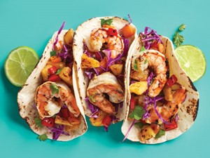 three grilled shrimp tacos in soft shell tortillas with lime slices on the side.