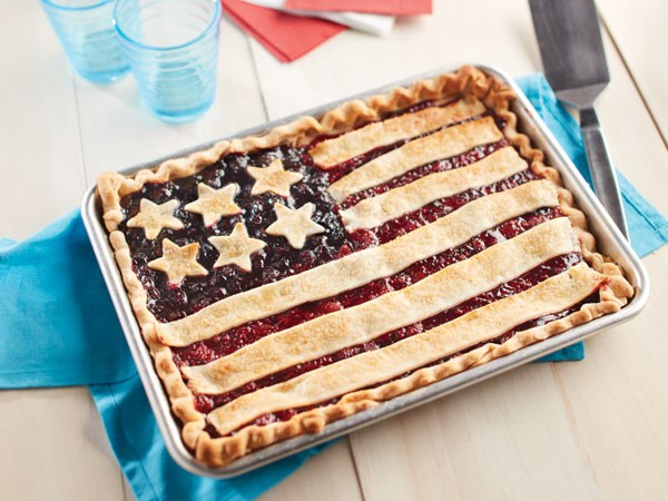 A sheet pan pie with a flag design made out of star-shaped pie crust and strips of pie dough.