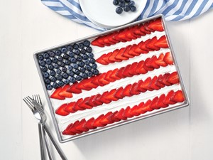 Flag pudding cake in a 13x9 baking pan topped with white frosting and decorated like an American flag using berries for stars and slices of strawberries for stripes.