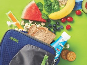 Lunchbox with whole grain bread, milk, cheese, fruit, avocado, and crackers