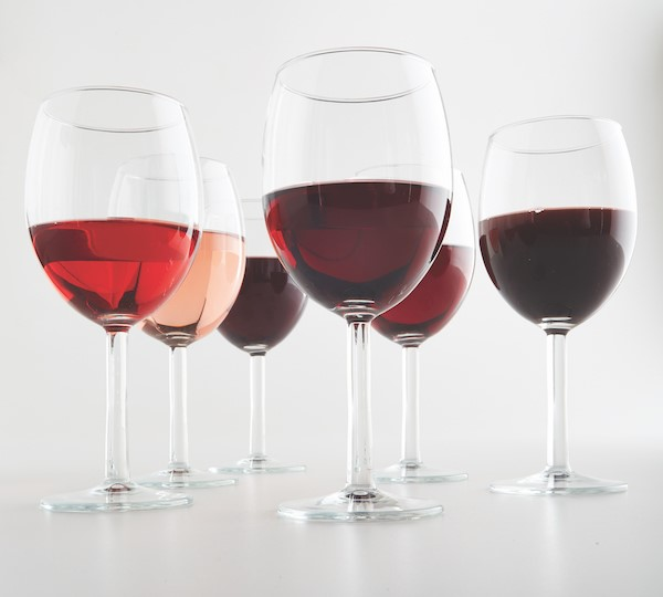 six wine glasses with different types of red wine