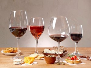 Four glasses of red wine with appetizers and finger foods