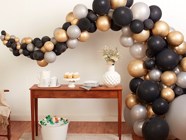 black and gold balloon garland over table