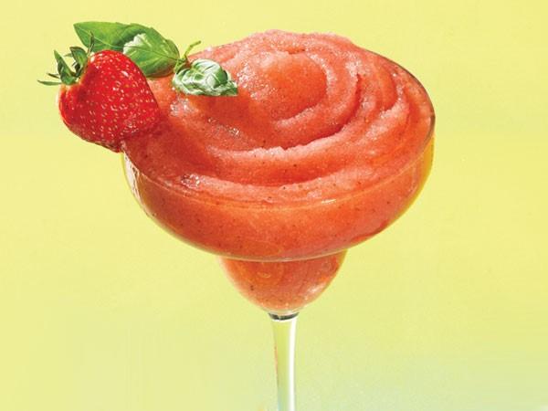 Frozen strawberry margarita in glass with strawberry basil garnish