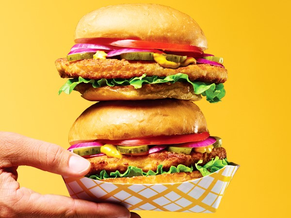 Two stacked breaded pork loin sandwiches in white and yellow takeout boats held in a hand on a yellow background.