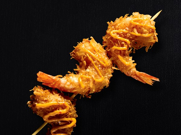 3 fried shrimp on a stick drizzled with sauce on a black background.