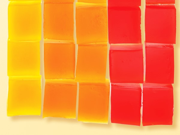 Yellow, orange, and red gelatin cubes organized in a grid on a light yellow background.